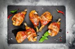 Speck wickelte Hühnerbeine auf einem schwarzen Hintergrund ein Stockfoto