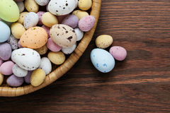 Speckled chocolate easter eggs in a basket. Still life photo of speckled candy covered chocolate easter eggs in a wicker basket on a rustic wooden table Royalty Free Stock Photos