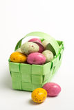 Speckled colourful easter eggs in a green wicker basket Stock Images