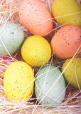 Speckled Easter Eggs. Speckled Pastel Colored Easter Eggs with straw on pink background Royalty Free Stock Photo