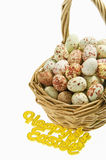 Speckled eggs in basket with Happy Easter sign on white background Royalty Free Stock Images