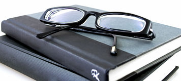 Specs and books. Black specs on a pile of two black books Royalty Free Stock Photo