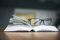 Specs and open book. Closeup of specs and open book on wooden desktop. Knowledge concept Royalty Free Stock Images