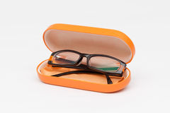 Spectacle case with eye glasses. Orange color spectacle case with eye glasses on white background stock image