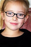 Spectacled Cutie. A smile and black eye glasses on a little blond cutie 5 year old girl. Shallow depth of field Stock Images