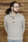 Spectacled fashion young man with beard in jeans and pullover on wood background Stock Photos