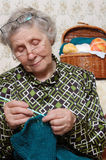 Spectacled grandmother to crochet cardigan. At home Stock Image