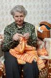 Spectacled Großmutter bindet Wolljacke Lizenzfreie Stockfotografie