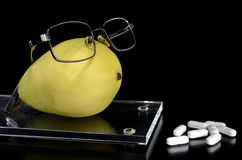 Spectacled pear on a tray and pills Stock Photography