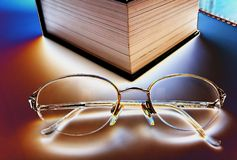 Spectacles. BIG BOOK AND  spectacles ON THE SHIT Royalty Free Stock Photos