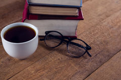 Spectacles, black coffee and book stack on wooden table. Close-up spectacles, black coffee and book stack on wooden table Stock Image