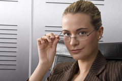 Spectacles blond. Young attractive businesswoman looking through spectacles in a modern office setting Royalty Free Stock Photos