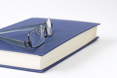 Spectacles on a blue book Stock Photo