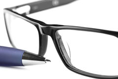 Spectacles and blue pen Royalty Free Stock Image