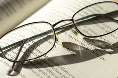 Spectacles on book page Stock Photos