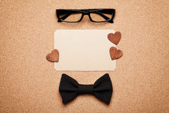 Spectacles, bowtie and empty paper blank in Happy Fathers Day, cork board background, top view, flat lay. Spectacles, bowtie and empty paper blank in Happy Stock Photos