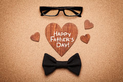Spectacles, bowtie and wooden heart with note Happy Fathers Day, cork board background, top view, flat lay Stock Images