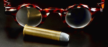 Spectacles and Bullet. Spectacles and brass riffle bullet Royalty Free Stock Image