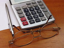 Spectacles and calculator. Spectacles, calculator, pencil and a piece of paper on brown wooden, desk royalty free stock photos
