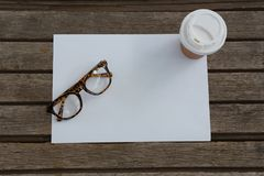 Spectacles, disposable glass and blank paper on wooden plank Stock Images