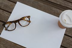 Spectacles, disposable glass and blank paper on wooden plank. Overhead of spectacles, disposable glass and blank paper on wooden plank Stock Photo