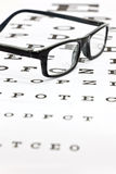 Spectacles on an eye test chart. Photo of black spectacles on an eye test chart Royalty Free Stock Images