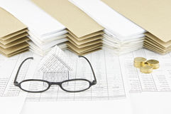 Spectacles and house with pile of gold coins Stock Image