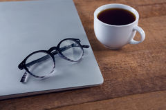 Spectacles on laptop with black coffee at desk. Close-up of spectacles on laptop with black coffee at desk Royalty Free Stock Photography