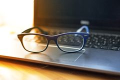Spectacles on a laptop on a wooden table stock photography