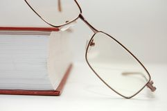 Spectacles laying on the closed book Stock Image