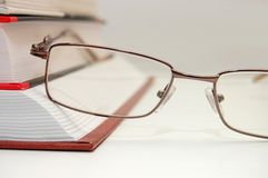 Spectacles laying on the closed book royalty free stock images
