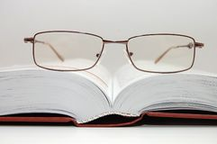 Spectacles laying on the open book Stock Photo