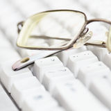 Spectacles lie on keyboard Royalty Free Stock Photo