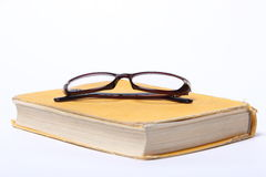 Spectacles lying on old book Stock Photos