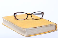 Spectacles lying on old book Royalty Free Stock Photos
