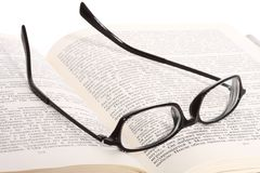 Spectacles lying on the opened book Stock Images