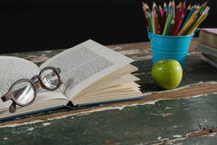 Spectacles on open book with pen holder and apple Stock Photo