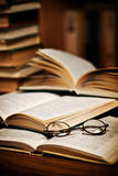 Spectacles on open books. Spectacles on pile of open books in library or study Royalty Free Stock Photo