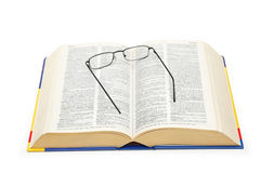 Spectacles over the open dictionary Royalty Free Stock Photo