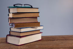 Spectacles and pencil on book stack Stock Photos
