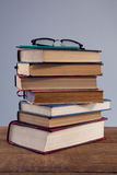 Spectacles and pencil on book stack Stock Images