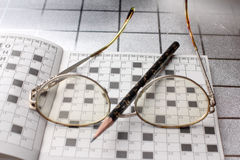 Spectacles, pencil, crossword Royalty Free Stock Photography