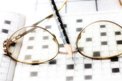 Spectacles, pencil, crossword Stock Photography