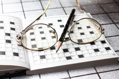 Spectacles, pencil, crossword Stock Photos