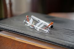 Spectacles and pencil on dossier stock photography