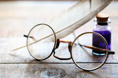 Spectacles And Quill. Art concept. Closeup of old spectacles near quill and ink-pot on wooden table Royalty Free Stock Photography