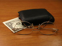 Spectacles and wallet. A gold-rimmed reading glass beside a wallet on top of a US dollar bill. Focused on the eyeglass stock photo