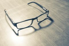 Spectacles on Wooden Table. Black-framed reading eyeglasses on a wooden table, decorated by a less intense shadow and bright light stock image