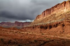 Spectaculaire kleurrijke rotsvormingen en epische onweerswolken over het Nationale Park van de Capitoolertsader in Utah stock foto's
