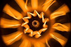 Glowing wire of a lightbulb from underneath. Spectacular abstract picture of a lightbulb from underneath, round light effect in yellow and orange royalty free stock image